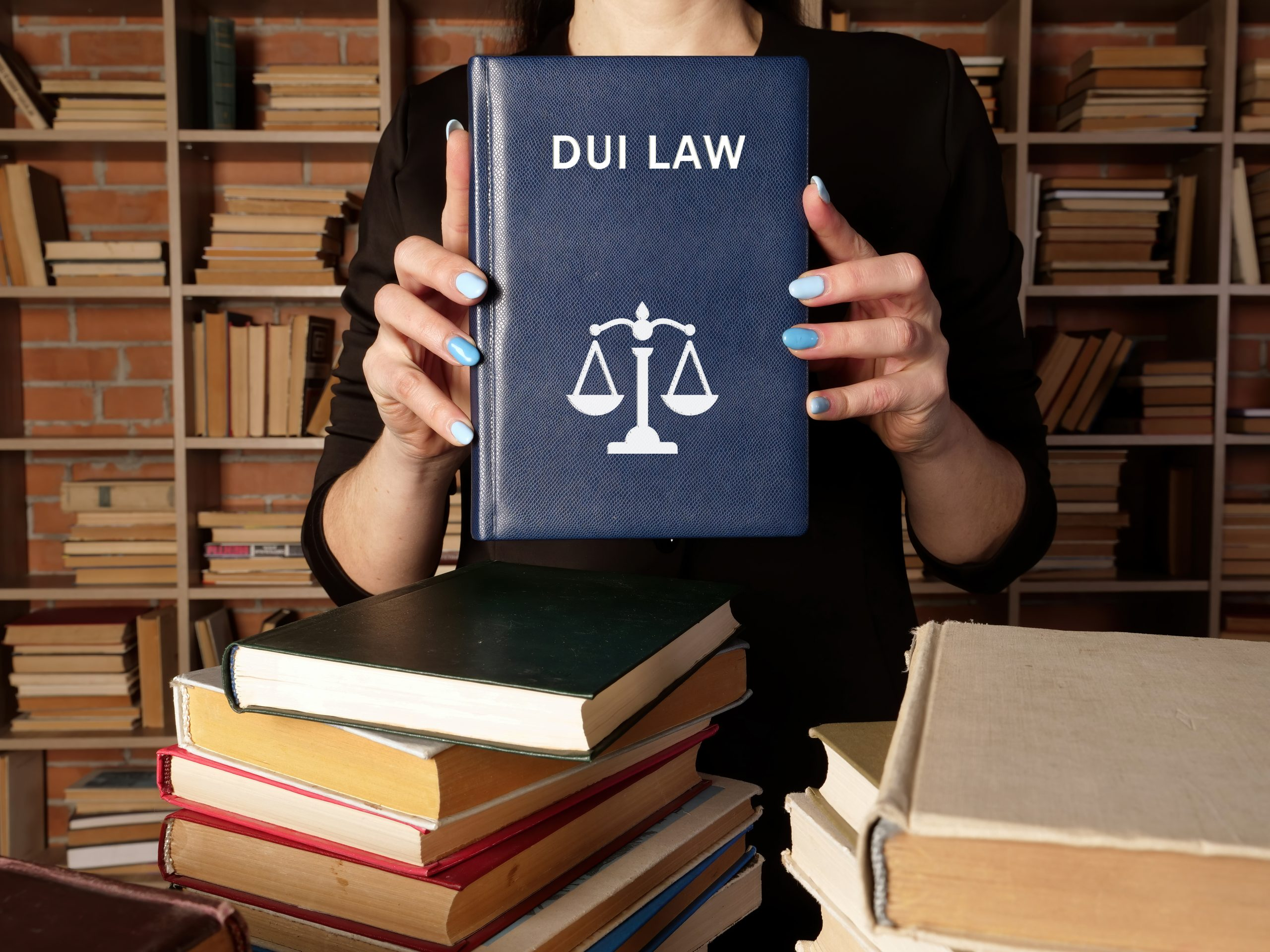 Lawyer holds DUI LAW book. Among other names, the criminal offense of drunk driving may be calleddriving under the influence